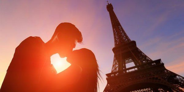 A couple kissing in front of Eiffel Tower in Paris